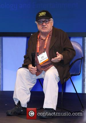 Danny Devito Danny Devito takes of his shoes and socks during an appearance at the Panasonic Booth at the 2013...