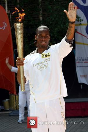 Didier Drogba carries the Olympic flame through Swindon Wiltshire, England - 23.05.12