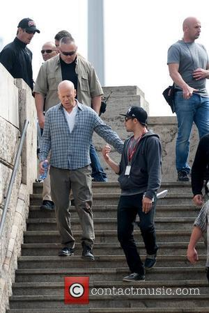 Bruce Willis walking down stairs with crew members on the film set of 'A Good Day to Die Hard' Hungary,...