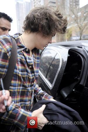 Harry Styles of One Direction is helped to his car by a security guard as he leaves his Manhattan hotel...