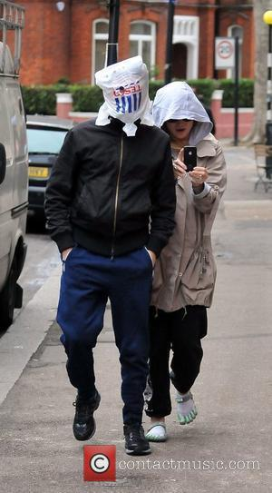 Matt Bellamy and Kate Hudson  walking in North London. Bellamy covered his head with a Tesco bag, looking out...