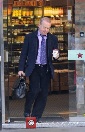 Ian Hislop eating breakfast and reading a daily newspaper at Pret A Manger before leaving with a coffee London, Engalnd...
