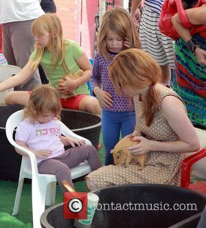 Isla Fisher and Elula Lottie Miriam Cohen holding a guinea pig Isla Fisher takes her daughters to a petting zoo...