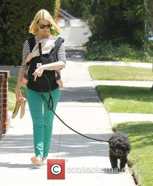 January Jones walks her dog barefoot whilst carrying her son Xander Los Angeles, California - 19.05.12