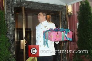 Flowers, presents and shopping bags from FAO Schwarz are carried out, as Jennifer Lopez and boyfriend Casper Smart are in...