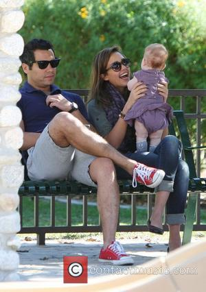 Jessica Alba and Cash Warren sit on a bench with Haven Warren during a family outing to the park Beverly...