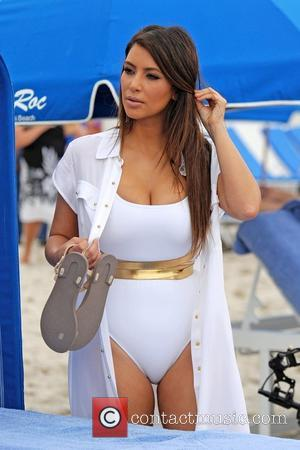Kim Kardashian seen at the beach wearing a white swimsuit and long cover-up  while filming the upcoming season of...