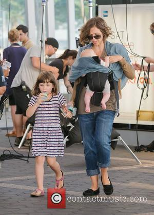 Maggie Gyllenhaal carries Gloria Ray Sarsgaard while daughter Ramona Sarsgaard walks alongside on the set of 'Very Good Girls.' New...
