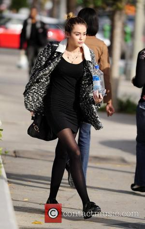 Miley Cyrus carrying a bottle of Fiji Water as she leaves California Pizza Kitchen in Studio City Los Angeles, California...