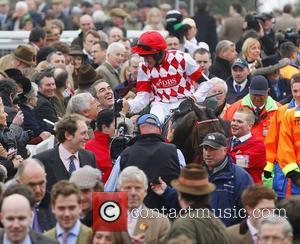 James Nesbitt congratulates jockey Barry Geraghty after his horse 'Riverside Theatre' won the 'Ryanair Steeple Chase' horse race on day...