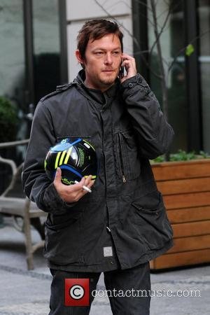 Norman Reedus talking on his cell phone and smoking a cigarette while walking in Manhattan New York City, USA -...