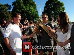 Melanie Chisholm and Chris Boardman exchange the Olympic flame as it passes through Liverpool Liverpool, England - 01.06.12