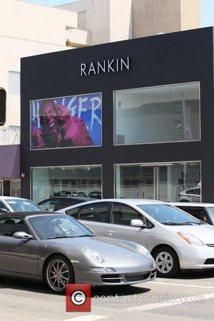 A large window display featuring a photograph of British rapper Dizzee Rascal laughing and 'flipping a double bird' is displayed...