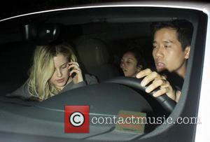 Riley Keough chats on her mobile phone in the car, as she leaves the Chateau Marmont hotel with friends Los...