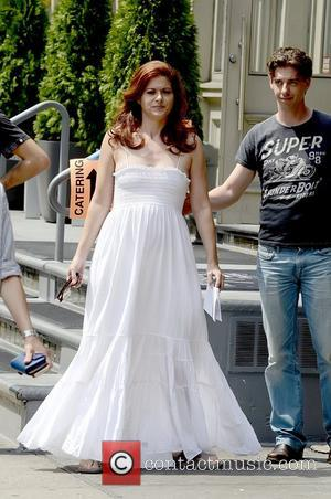 Debra Messing wearing a long white dress during filming for the TV show 'Smash' in SoHo New York City, USA...
