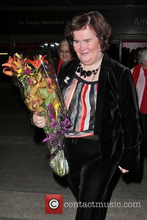 Susan Boyle carries a large bouquet of flowers in her arms as she arrives at LAX, Los Angeles International Airport,...