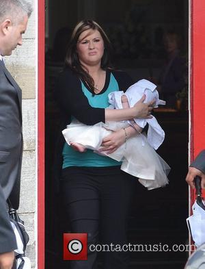 Aoife Foden, the daughter of Una Healy and Ben Foden, leaving the church in the arms of a relative The...