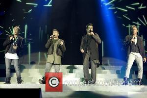 Kian Egan, Shane Filan, Mark Feehily and Nicky Byrne of Westlife perform live on stage at the SECC during their...