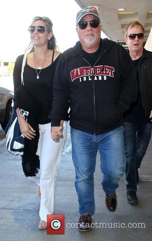 Billy Joel - Billy Joel holds hands with his wife Alexis Roderick, as they arrive at Los Angeles International LAX...