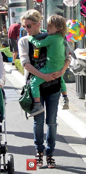 Kathleen Robertson and William Robert Cowles - Canadian actress Kathleen Robertson carries her son as she talks with a friend...
