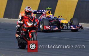Casey Stoner leads Mark Webber's Red Bull F1 car during the Bike v Car V F1 car showdown - Top...