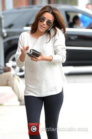 Eva Longoria - Eva Longoria juggles two cellphones and makes her calls while walking to an office building in Beverly...