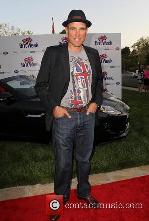 Vinnie Jones, trilby, hat, grey, print, t shirt, union jack, jacket, jeans, shoes, brown, hands in pocket and couple