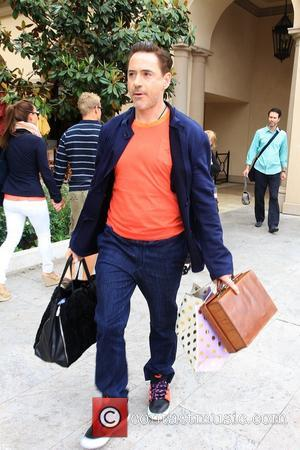 Robert Downey Jr - Robert Downey Jr carries some luggage to his SUV for an outing with his wife Susan...