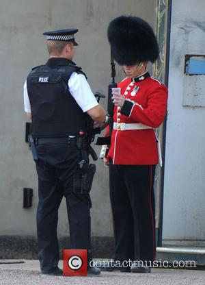 Policeman and Royal Guard - A policeman gives a Royal Guard some water as he feels the heat from the...