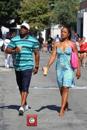 Laila Ali and Curtis Conway - Laila Ali carrying an oversized pink handbag out and about with Curtis Conway at...