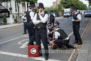 Police - London, UK. 26/08/13. Police officers detaining a man during the Notting Hill Carnival. - London, UK, United Kingdom...