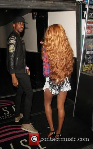 Azealia Banks - Alexandra Burke hides behind a self portrait painting with her male companion as they leave Rise Superclub...