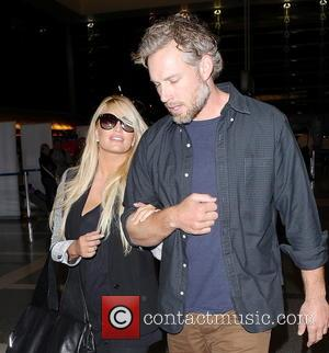 Jessica Simpson and Eric Johnson - Jessica Simpson and husband Eric Johnson arrive at LAX airport to catch a departing...
