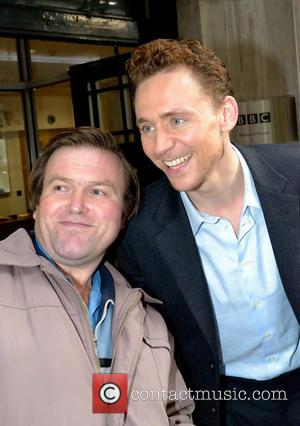 Tom Hiddleston - Tom Hiddleston poses for photographs with fans waiting outside after leaving the BBC Radio 2 studios at...