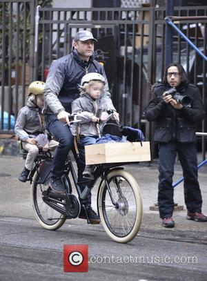 Liev Schreiber - Liev Schreiber takes his sons to school, giving them a ride on his bike. Originally wearing the...