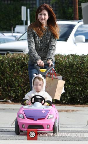 Alyson Hannigan and Keeva Jane Denisof - Alyson Hannigan and husband Alexis Denisof push their daughter Keeva in a toy...
