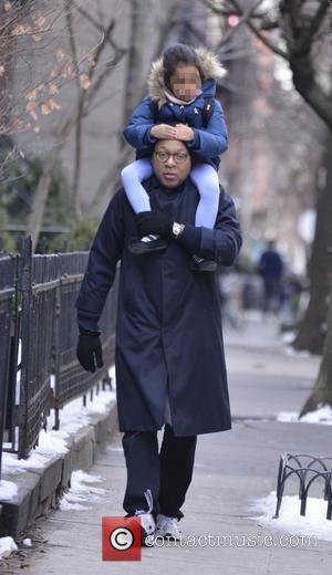 Wynton Marsalis - Wynton Marsalis carrying his daughter on his shoulders as he strolls along a sidewalk in Manhattan -...