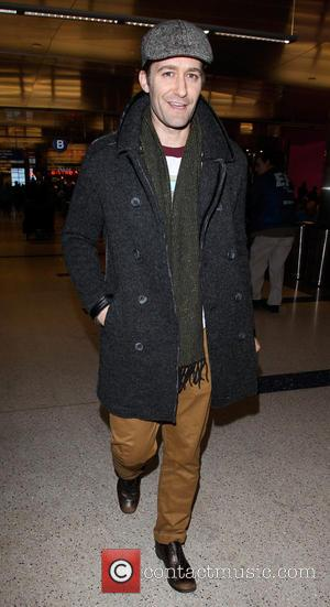 Matthew Morrison arrives at Los Angeles International airport (LAX) wearing a rain coat and flat cap and walking in scruffy...