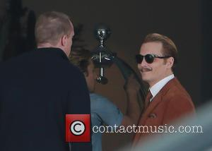 Johnny Depp - Johnny Depp filming on the set of 'Mortdecai' carrying a gold top cane and sporting a curly...