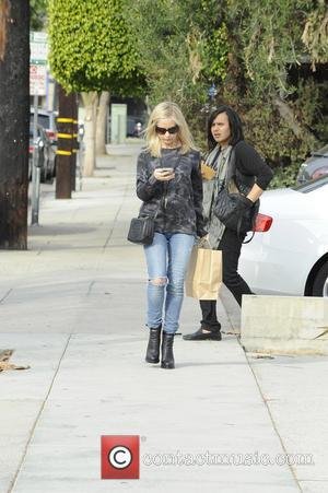 Sarah Michelle Gellar - Sarah Michelle Gellar is all smiles as she texts on her cellphone while leaving Andy LeCompte...