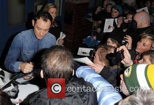 Jude Law - Jude Law signs autographs for waiting fans as he leaves the Noel Coward Theatre, having appeared in...