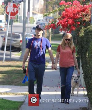Jon Hamm and Jennifer Westfeldt - Jon Hamm wearing a t-shirt supporting the podcast Sklarbro Country holds hands on a...