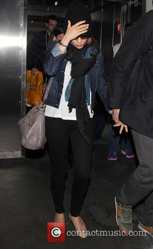 Mila Kunis - Ashton Kutcher and Mila Kunis arrive at Los Angeles International (LAX) airport - Los Angeles, California, United...