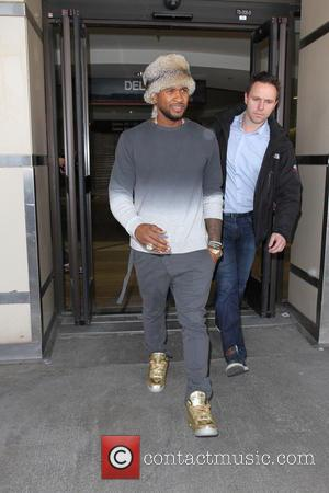 Usher - Usher arrives at Los Angeles International Airport (LAX) wearing gold sneakers and a round fur hat - Los...