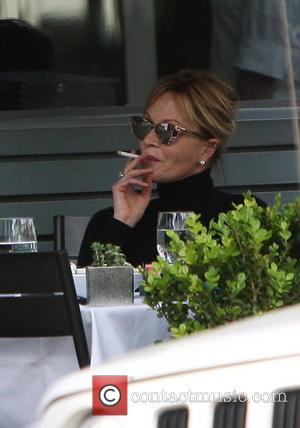 Melanie Griffith - Melanie Griffith smoking a cigarette at the table while out for lunch with a friend in West...