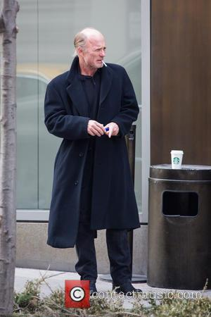 Ed Harris - An unshaven Ed Harris lights up a cigarette while taking a coffee break, resting his cup on...