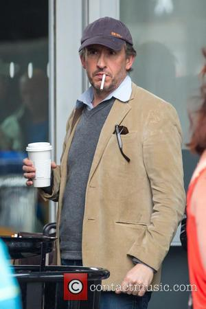 Steve Coogan - Steve Coogan smokes a cigarette upon arriving at John F. Kennedy International Airport (JFK) - New York...
