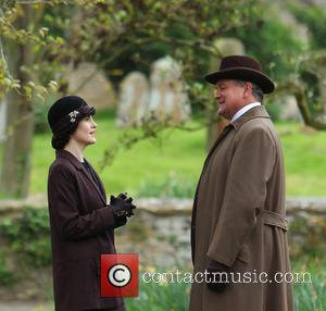 Michelle Dockery and Hugh Bonneville - The cast of Downton Abbey film scenes on location outside a churchyard - Bampton,...