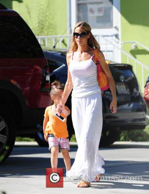 Denise Richards and Eloise Sheen - Denise Richards in a white see-through cotton maxi dress carries her daughter Eloise in...