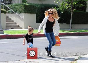 Denise Richards and Eloise Sheen - Denise Richards walking in Ugg boots and jeans carries her daughter Eloise in her...